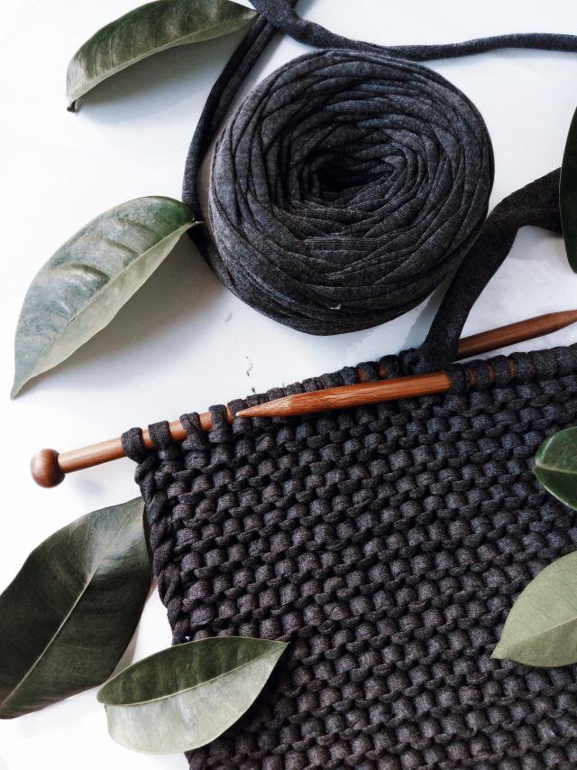 black yarn knitted, laid flat on white background